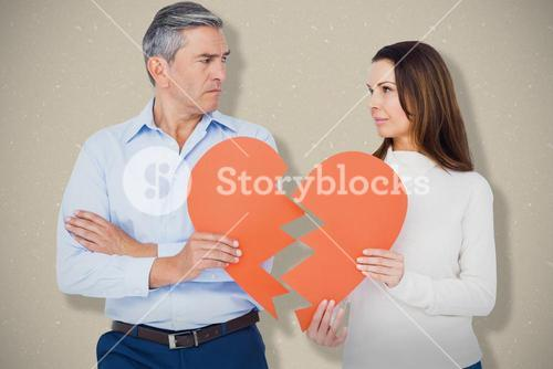 Composite image of couple holding broken heart shape paper