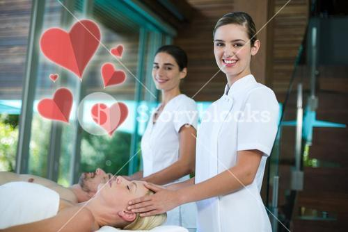 Composite image of two masseuses giving  head massage with love hearts