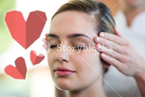 Composite image of woman receiving temple massage with love hearts