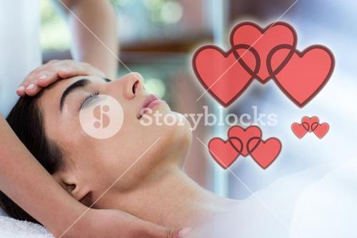 Composite image of woman receiving a massage with love hearts