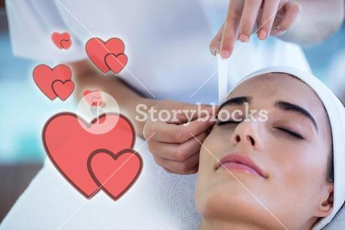 Composite image of a woman getting eyebrows shaped with love hearts