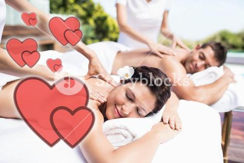 Composite image of a young couple receiving a back massage with love hearts