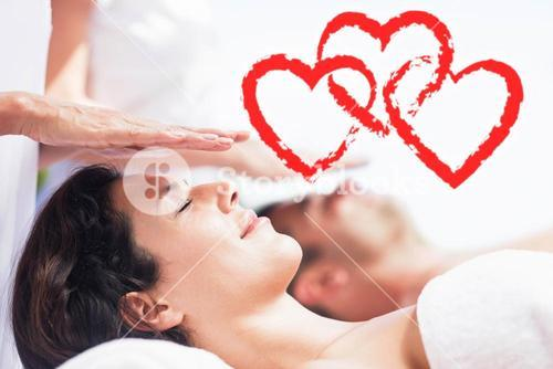 Composite image of a couple receiving a massage with love hearts