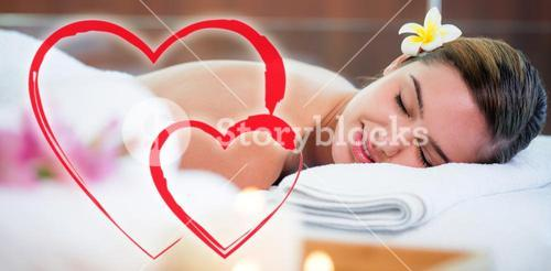 Composite image of a lying woman on a massage table with love hearts