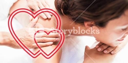 Composite image of a woman receiving a massage with love hearts
