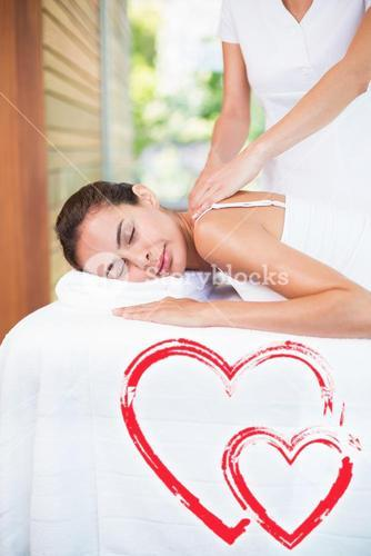 Composite image of pwoman receiving a massage love hearts