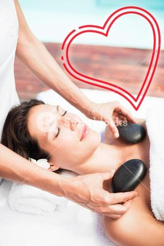 Composite image of woman receiving a massage with love heart