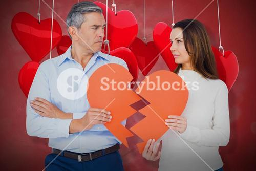 Composite image of couple holding broken heart shape paper 3d