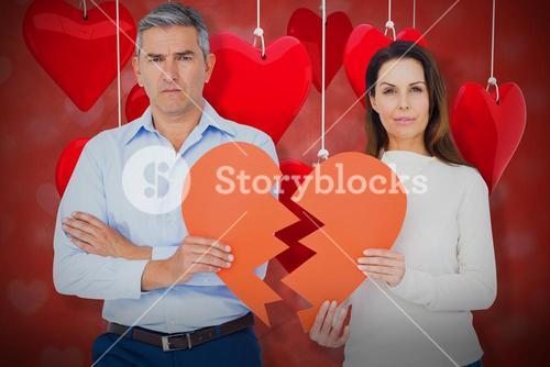 Composite image of portrait of couple holding broken heart shape paper 3d