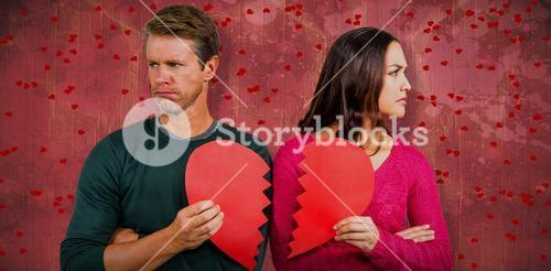 Composite image of serious couple holding cracked heart shape