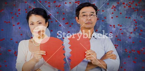 Composite image of couple holding broken heart