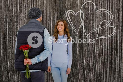 Composite image of man hiding roses behind back from woman