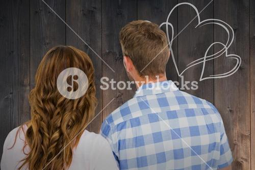 Composite image of rear view of young couple standing