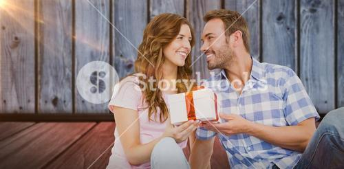 Composite image of man giving gift to woman