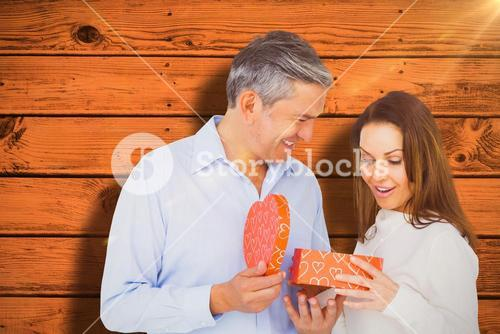 Composite image of happy couple opening present