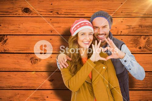 Composite image of happy young couple making heart shape with hands