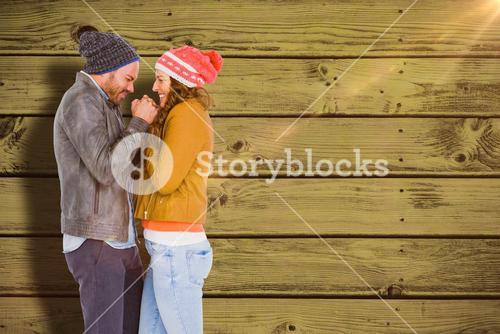 Composite image of young couple in warm cloth standing face to face and shivering