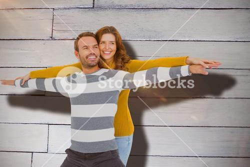 Composite image of young couple standing with arms outstretched