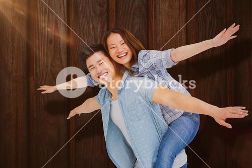 Composite image of portrait of happy couple with arms outstretched