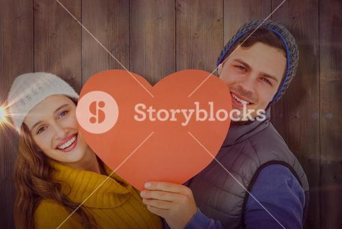 Composite image of happy couple holding heart shape paper