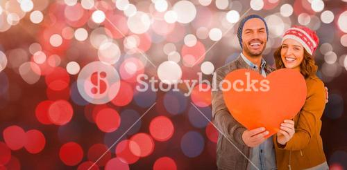 Composite image of happy young couple holding heart shape paper