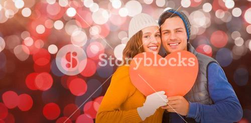 Composite image of portarit of happy couple holding paper heart
