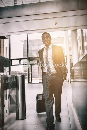 Happy businessman walking with suitcase