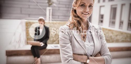 Businesswoman standing with arms crossed in office premises