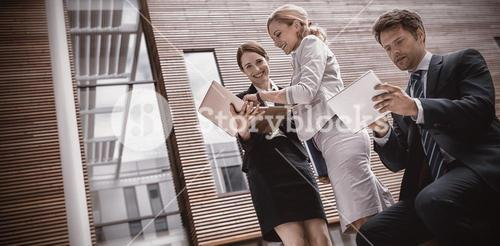 Businesspeople using laptop and tablet