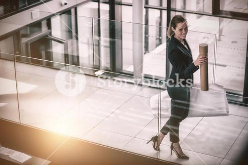 Businesswoman standing at office corridor with chart holder