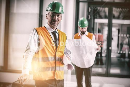 Architect in hard hat standing with blueprint in office corridor