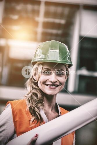 Portrait of architect woman in hardhat holding blueprints