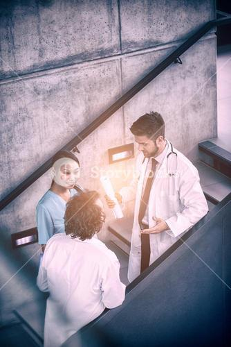 Doctors discussing with nurse on stairs