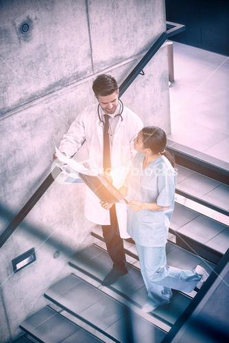 Happy doctor and nurse discussing over report while climbing down stairs
