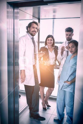 Doctors and businesswoman standing in elevator