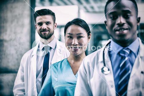 Confident nurse standing with colleagues