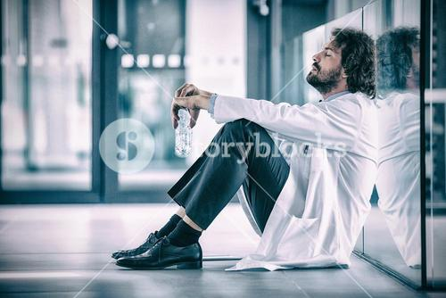 Side view of worried doctor sitting on floor