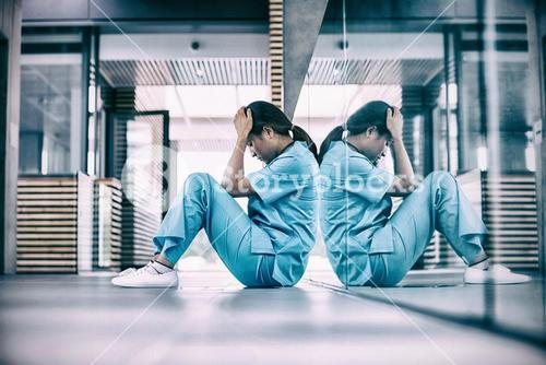 Stressed nurse sitting on floor