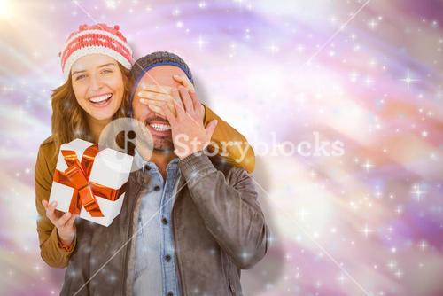 Composite image of portrait of woman giving surprise gift to man