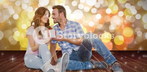 Composite image of happy man giving gift to woman