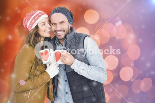Composite image of happy young couple holding coffee mug