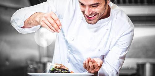 Chef sprinkling spices on dish