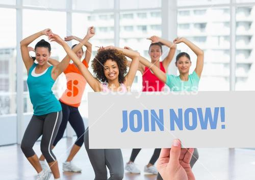 Happy women dancing in fitness studio with hand holding placard in foreground