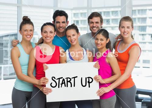 Fit men and women holding placard with start up text in fitness studio