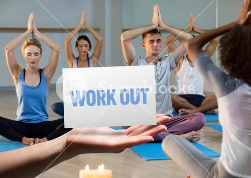 Men and women practicing yoga in fitness studio with hand holding placard in foreground