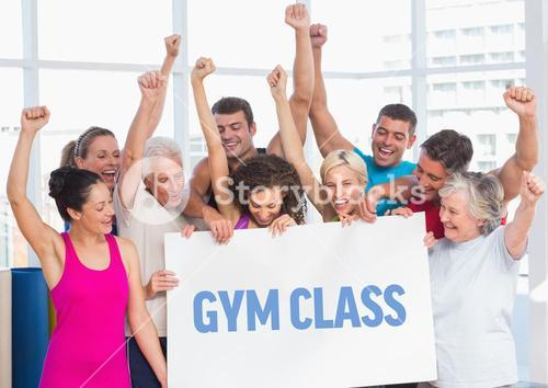 Fit men and women holding placard with gym class text in fitness studio