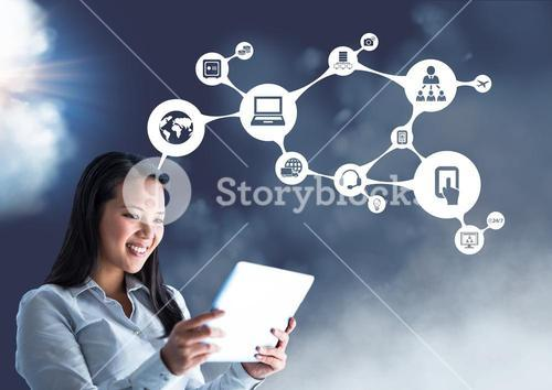 Smiling businesswoman using digital tablet against connecting icons