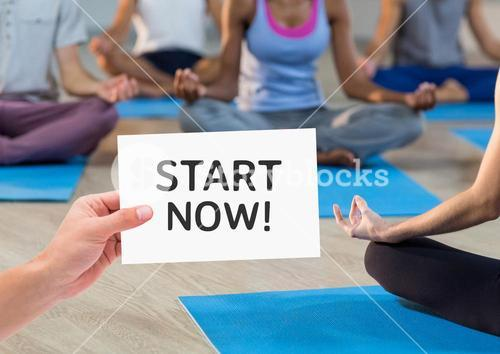 Woman hand showing start now text written on page in fitness studio