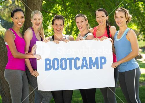 Fitness women hold placard with text boot camp in the park