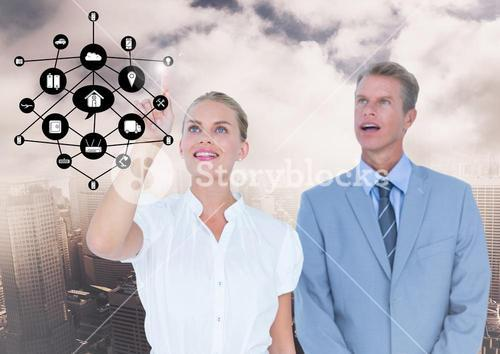 Businesspeople using digital screen with digitally generated icon